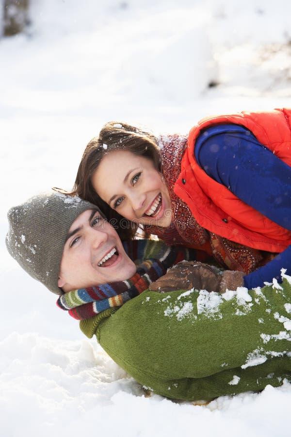 Jugendpaare, die Spaß im Schnee haben lizenzfreie stockfotos