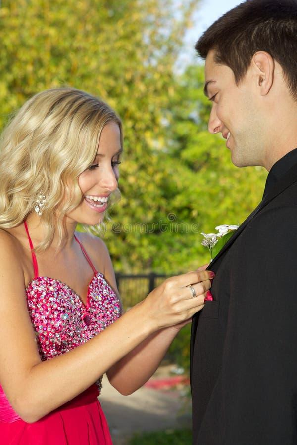 Jugendpaare, die zum Abschlussball sich setzt auf Boyfriend& x27 gehen; s-Boutonniere lizenzfreies stockbild