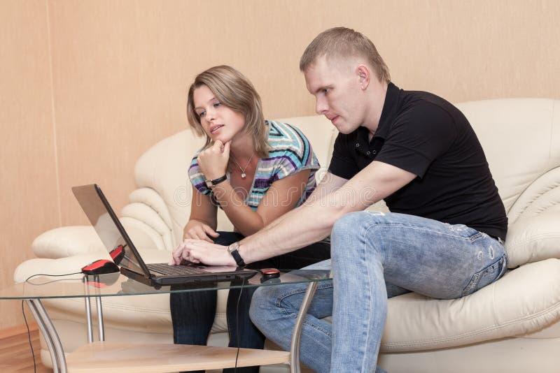 Jugendpaarmitteilung im Sozialen Netz, beim im inländischen Raum zusammen sitzen, Laptop auf Glastisch ist stockfoto