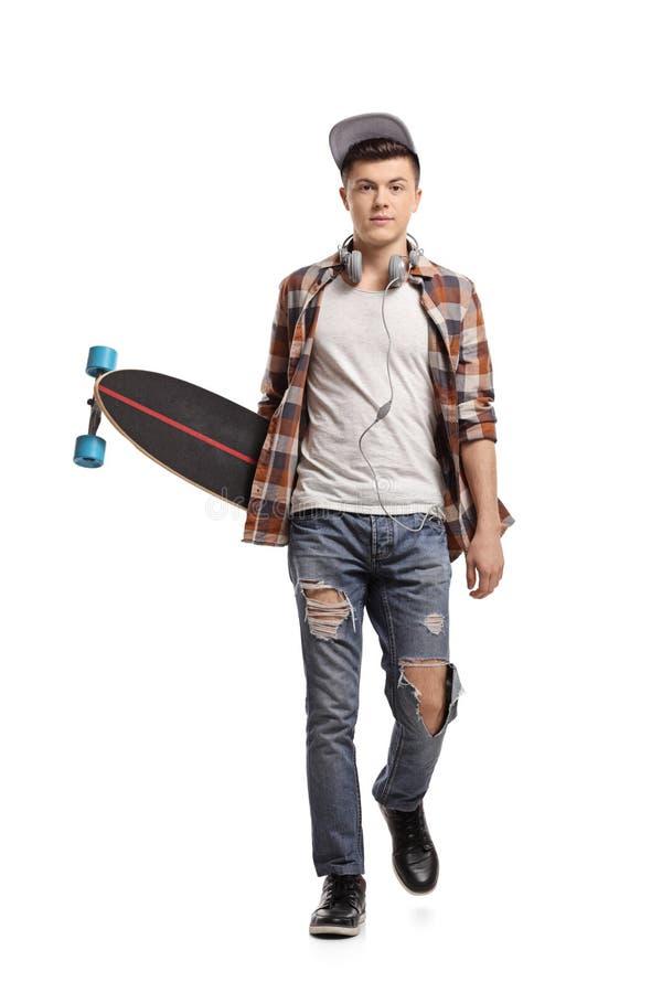 Jugendschlittschuhläufer mit einem longboard gehend in Richtung zur Kamera stockfotografie