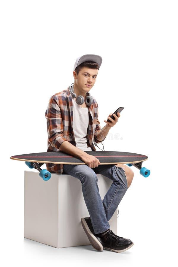 Jugendschlittschuhläufer mit einem Telefon und einem longboard, die auf einem Würfel sitzen lizenzfreies stockfoto