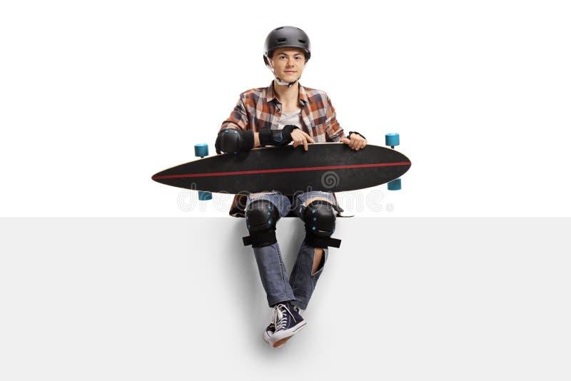 Jugendschlittschuhläufer mit Schutzausrüstung und einem longboard Sitzen lizenzfreie stockfotografie