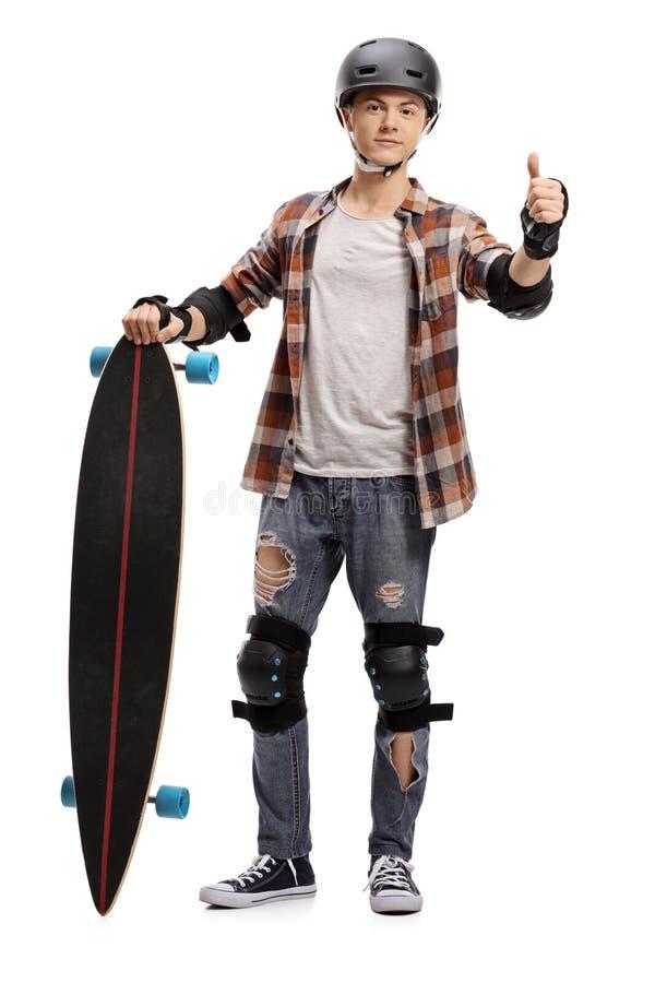 Jugendschlittschuhläufer mit Schutzausrüstung und einer longboard Herstellung stockfoto