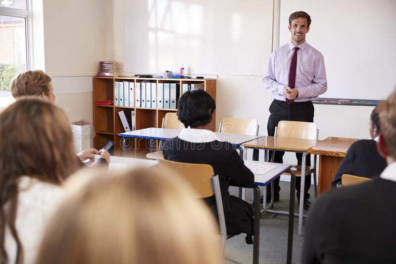 Jugendstudenten, die auf männlichen Lehrer In Classroom hören lizenzfreies stockbild
