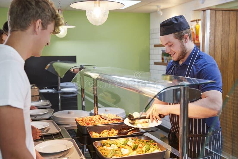 Jugendstudenten, die Mahlzeit in der Schulkantine gedient werden stockfotos