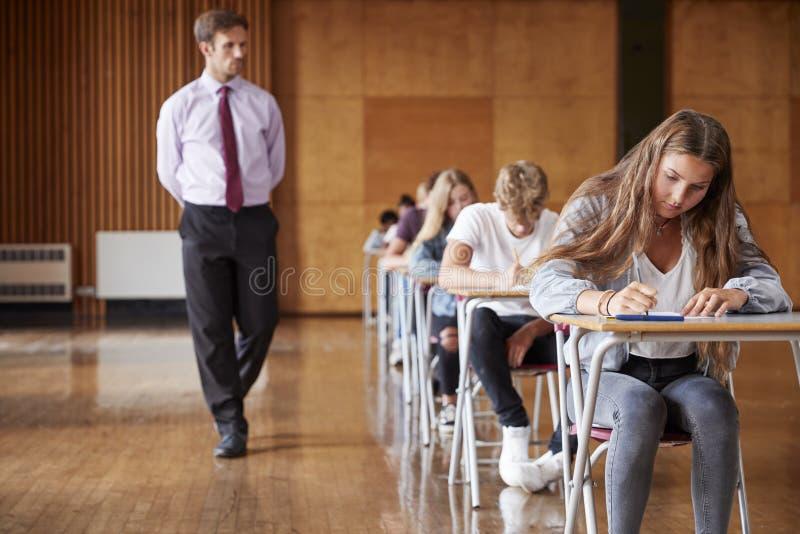 Jugendstudenten, die Prüfung mit Lehrer Invigilating sitzen lizenzfreie stockfotografie
