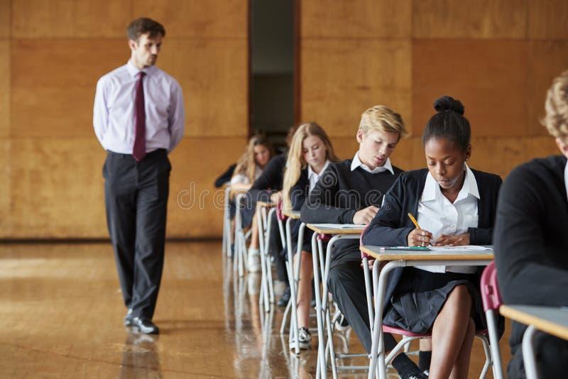 Jugendstudenten, die Prüfung mit Lehrer Invigilating sitzen stockfotos