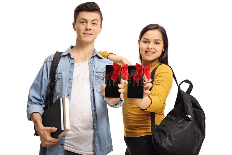 Jugendstudenten, welche die Telefone eingewickelt mit roten Bändern als pres zeigen lizenzfreies stockfoto