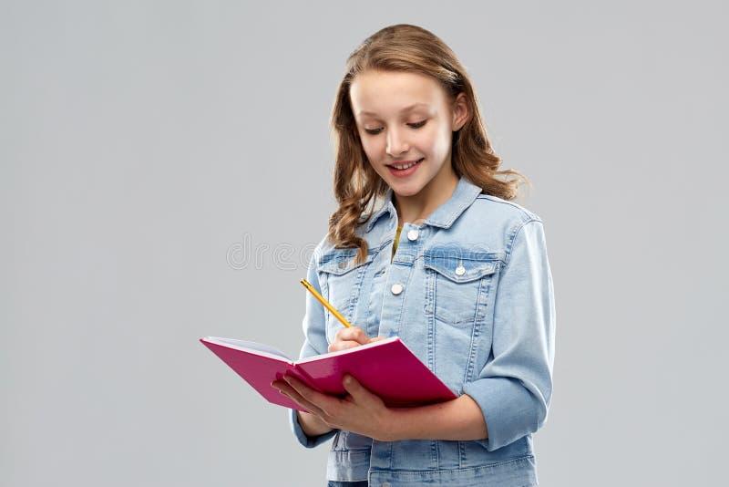 Jugendstudentenmädchenschreiben zum Tagebuch oder zum Notizbuch lizenzfreie stockfotos