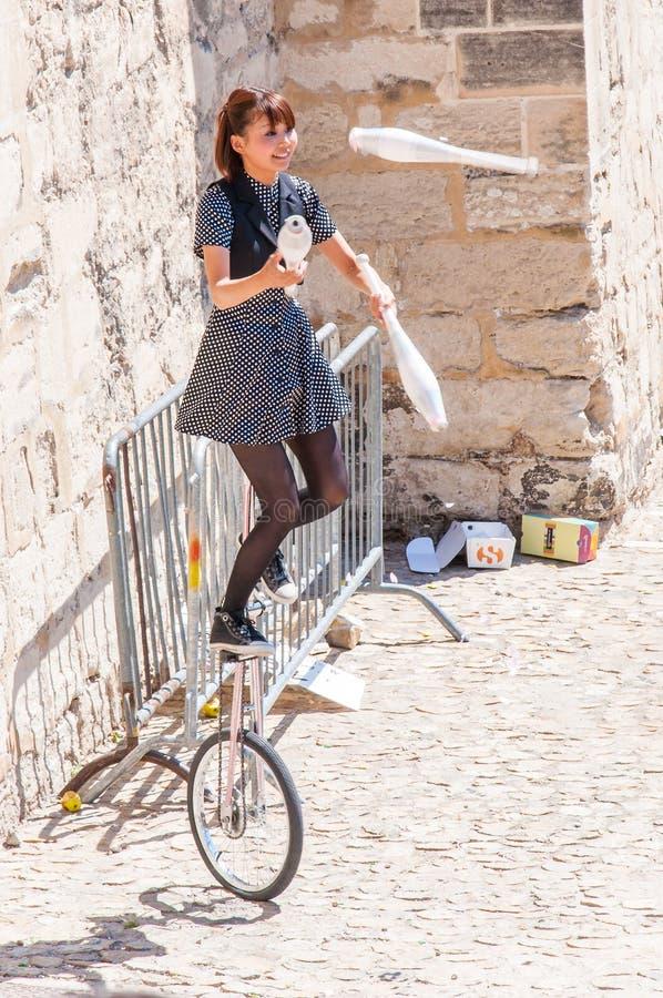 Juggler asiático da menina do artista da rua que manipula com as boliches de nove garrafas na bicicleta um-rodada na cidade velha imagem de stock