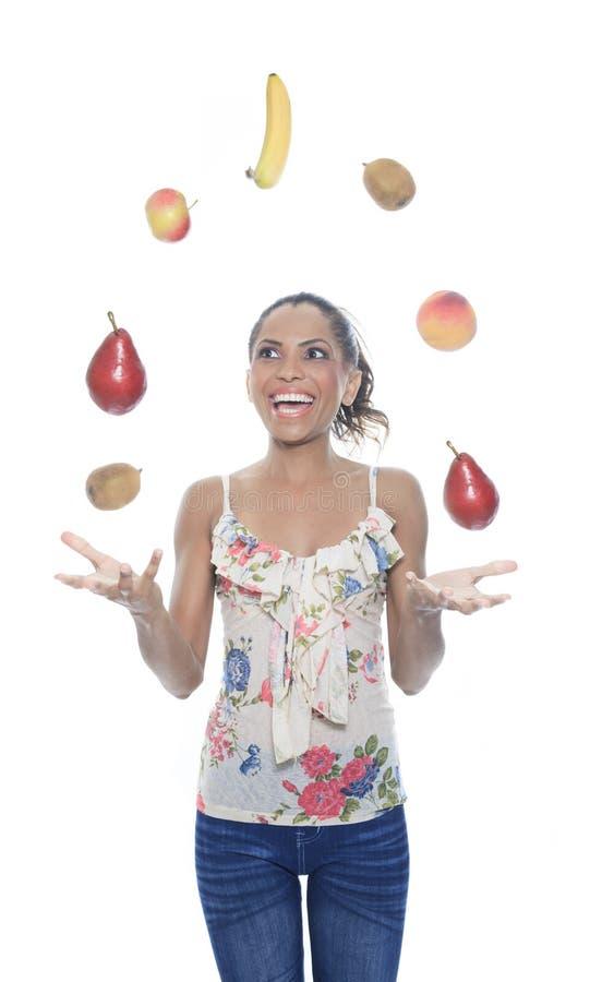 Juggler da pessoa do mulato com fruto no estúdio imagens de stock royalty free