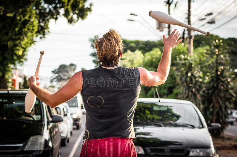 A juggler performing on the street. RIBEIRAO PRETO, BRAZIL - FEBRUARY 13, 2015: A juggler performing on the street while the cars are stopped by the red light stock image