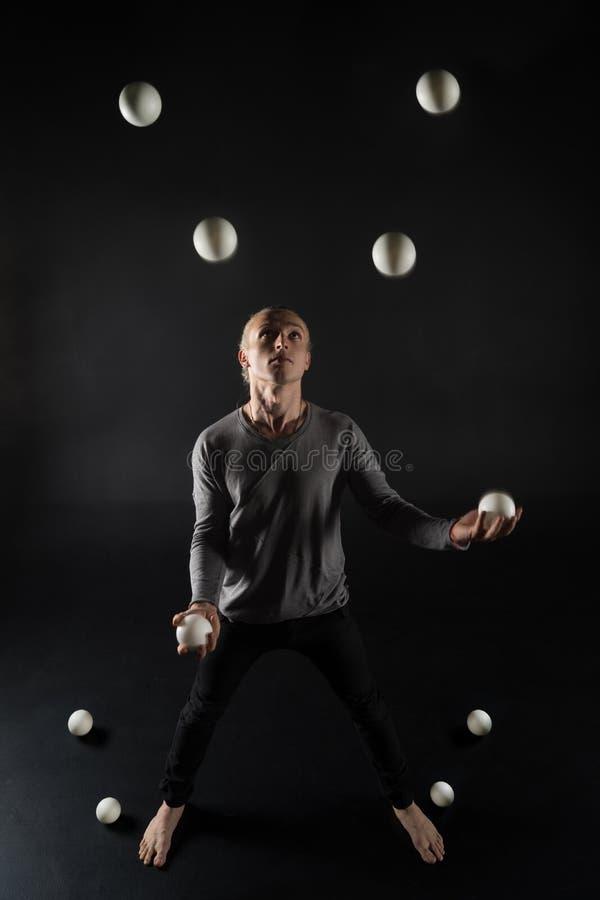Juggler van het blondehaar met witte ballen op zwarte achtergrond stock foto
