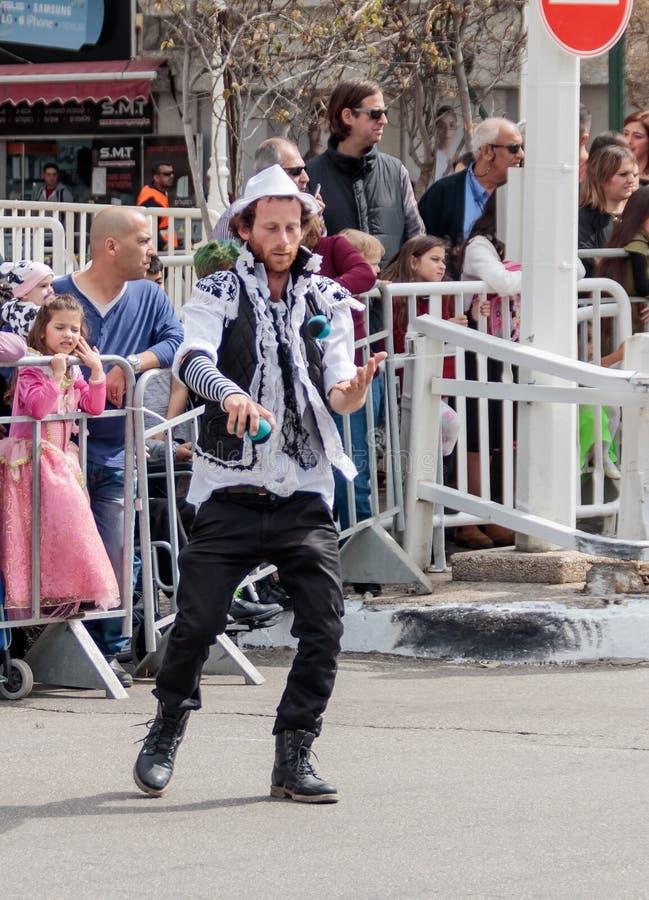 Juglar con las bolas coloreadas que camina a lo largo de la calle en el carnaval imágenes de archivo libres de regalías