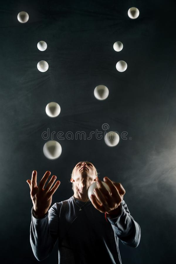 Juglar rubio con las bolas blancas en fondo negro imagen de archivo