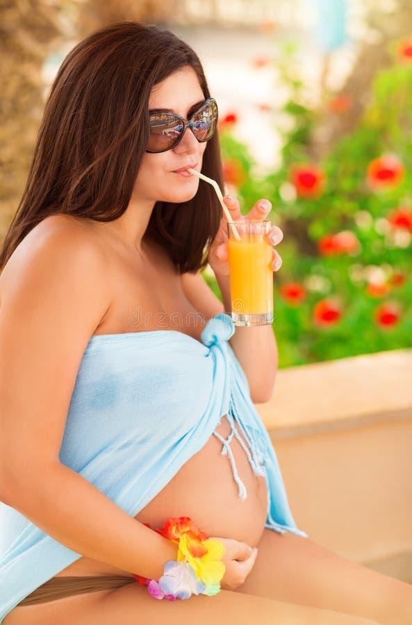 Jugo de consumición de la mujer embarazada fotografía de archivo libre de regalías