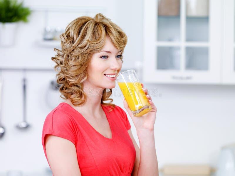 Jugo de consumición de la mujer en la cocina imagen de archivo libre de regalías