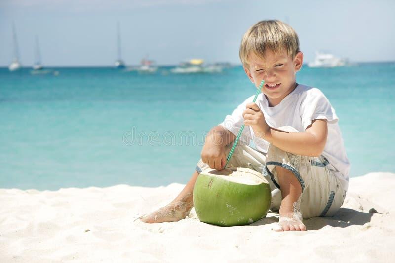 Jugo de consumición del coco del muchacho en fondo del mar fotos de archivo