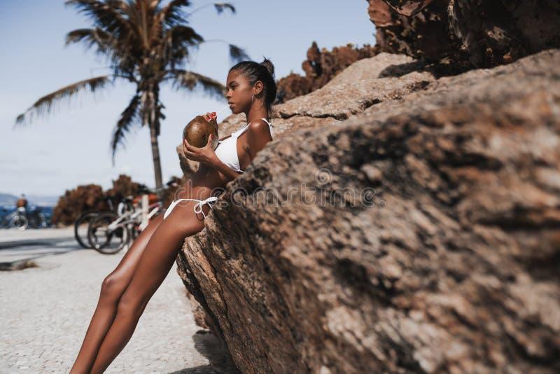 Jugo de consumición del coco de la muchacha astuta del Afro foto de archivo libre de regalías