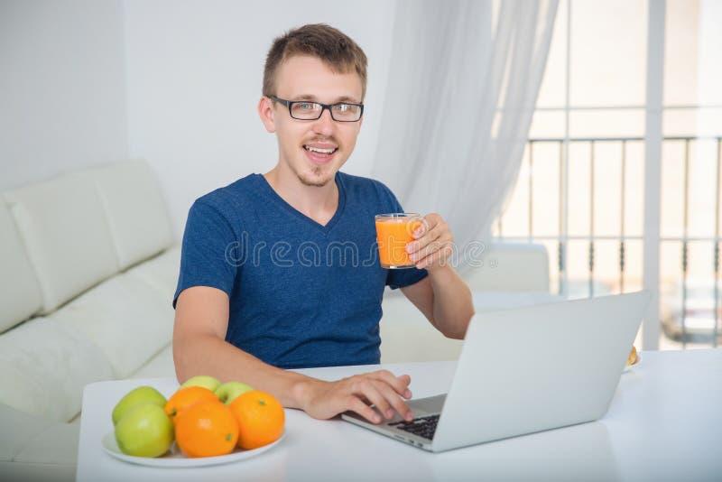 Jugo de consumición del hombre que sienta la tabla con un ordenador portátil fotografía de archivo libre de regalías
