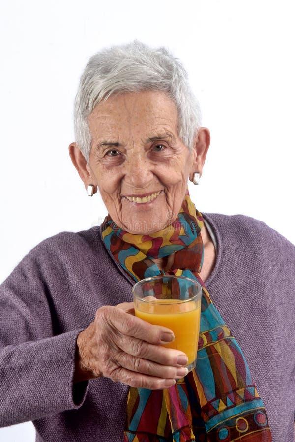 Jugo de consumición de la mujer mayor en el fondo blanco fotos de archivo