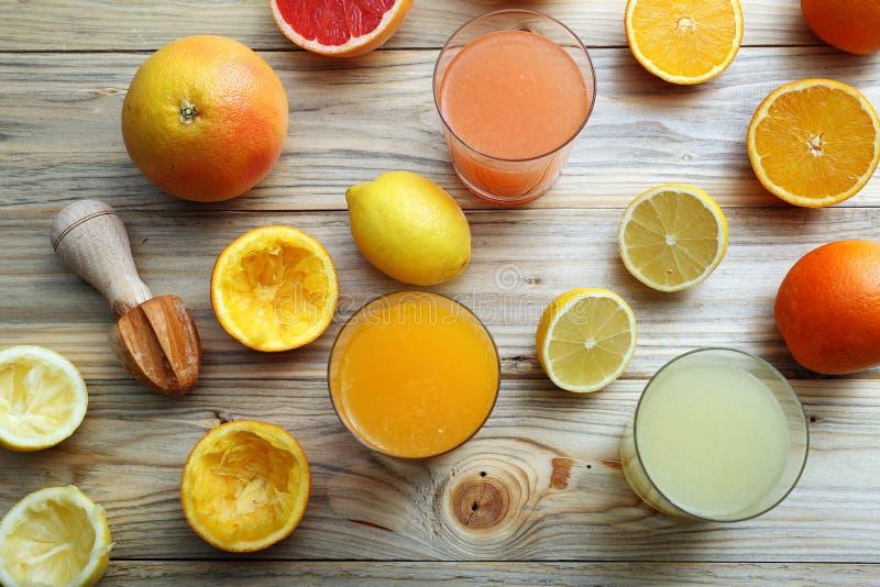Jugo de la fruta cítrica tres vidrios con el limón y el pomelo anaranjados de la fruta fotos de archivo libres de regalías