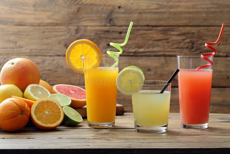 Jugo de la fruta cítrica tres vidrios con el limón y el pomelo anaranjados de la fruta imagen de archivo libre de regalías