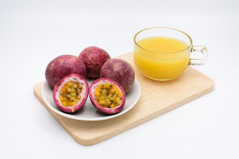 Jugo de la fruta de la pasión con la fruta de la pasión en una taza en un de madera fotografía de archivo