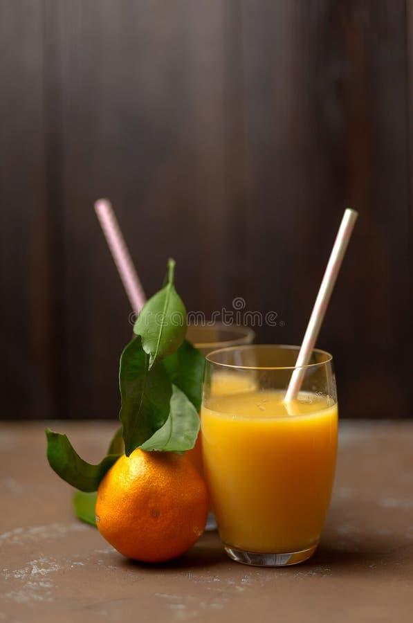 Jugo de mandarina. Tangerinas con hojas. Vitamina natural foto de archivo
