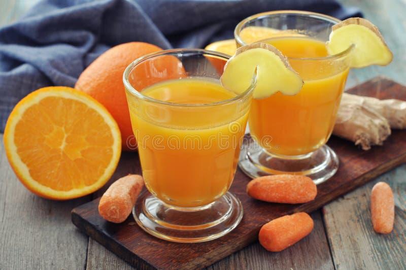 Jugo de la naranja y de zanahoria con el jengibre fotografía de archivo libre de regalías