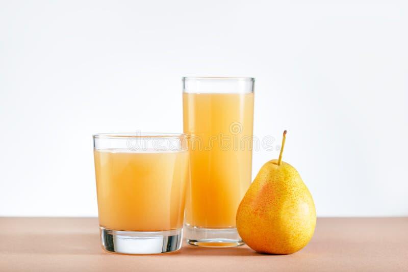 Jugo de la pera con las frutas frescas en la tabla fotografía de archivo