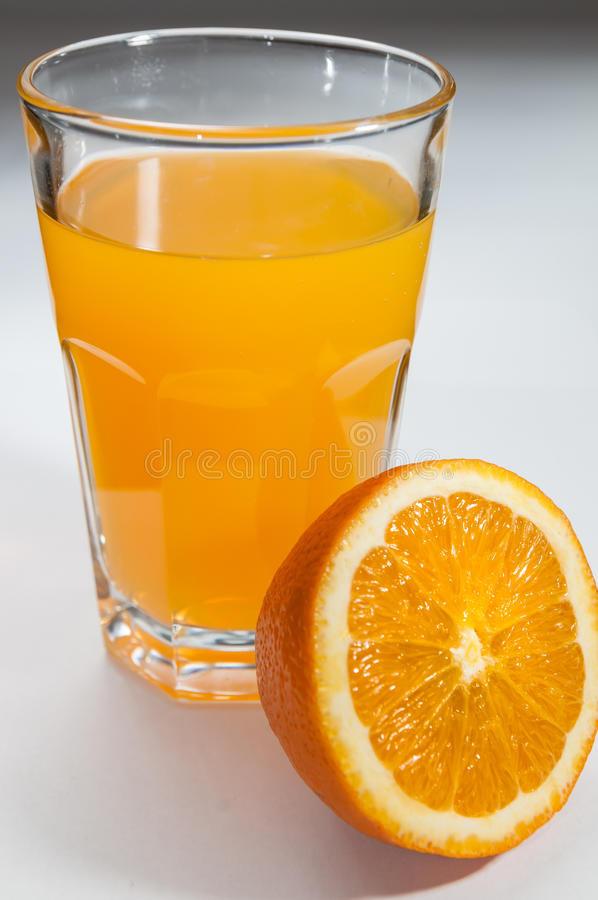 Jugo de Orage en un vidrio y a medias anaranjado por otra parte foto de archivo