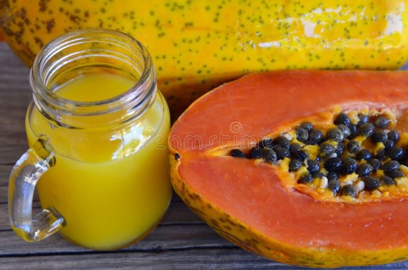 Jugo de papaya fresco en una fruta madura de la papaya del tarro de cristal en la tabla de madera vieja Bebida, detox, dieta o co imagenes de archivo