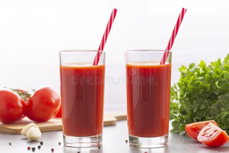 Jugo de tomate con albahaca y especias Vidrios con el jugo de tomate y los tomates frescos fotos de archivo libres de regalías