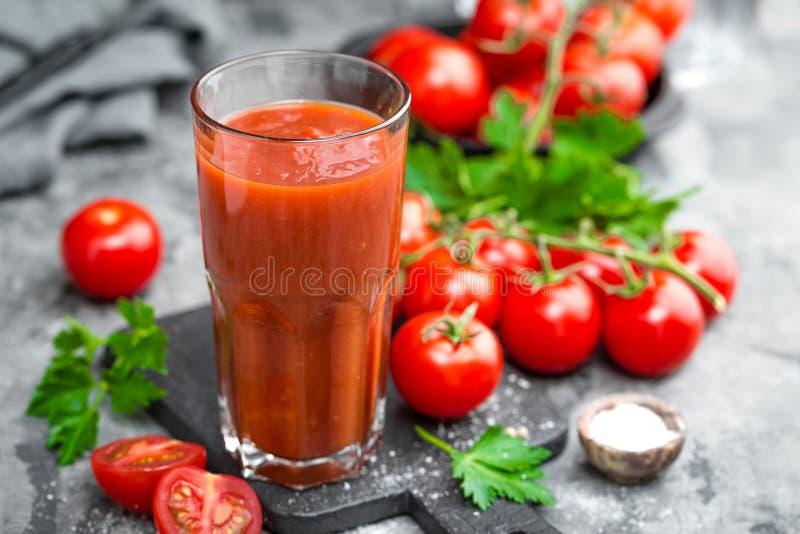 Jugo de tomate y tomates frescos fotos de archivo