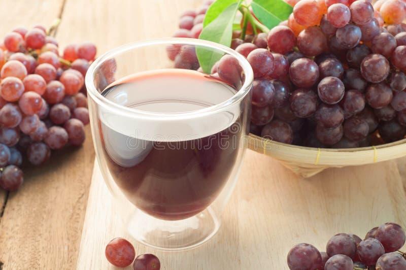 Jugo de uva y grupo de uvas en la cesta de bambú imagenes de archivo