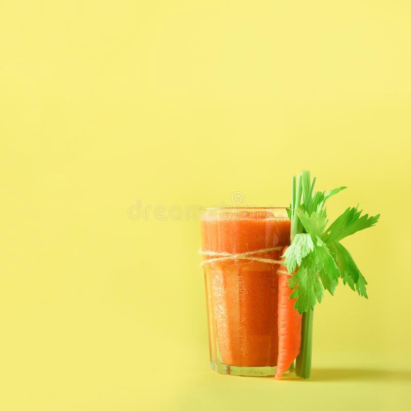 Jugo de zanahoria anaranjado con las zanahorias, apio en fondo amarillo Cosecha cuadrada Smothie de las verduras frescas en vidri imágenes de archivo libres de regalías