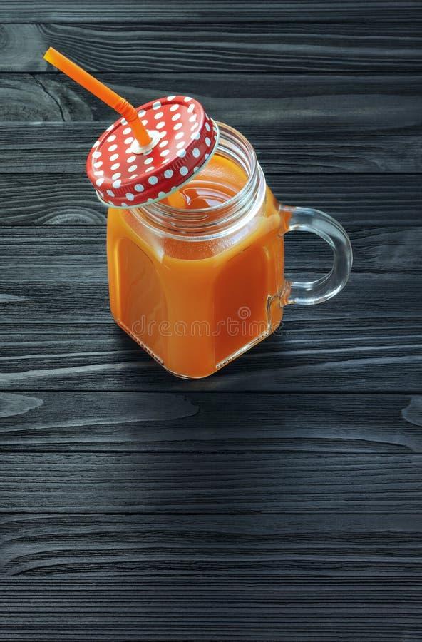 Jugo de zanahoria en un tarro de cristal con la manija en una tabla de madera negra foto de archivo