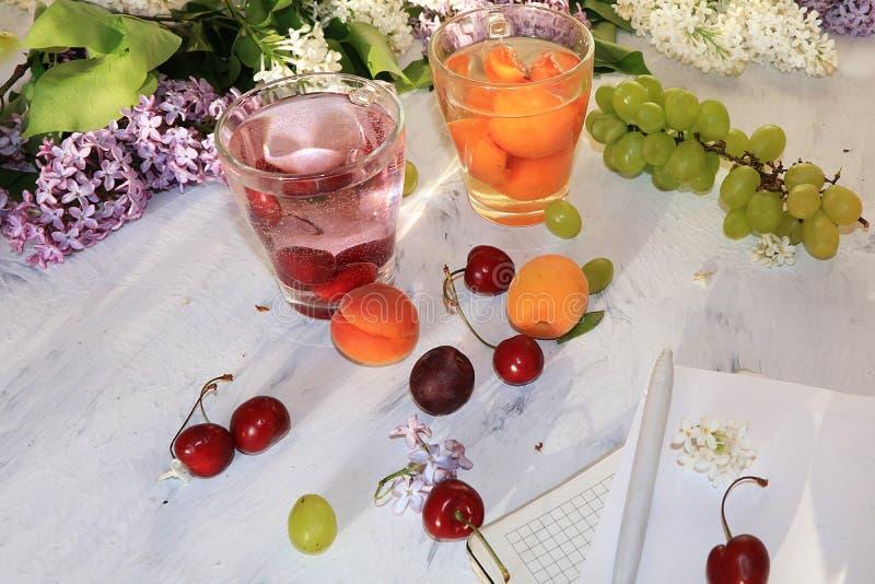 Jugo del albaricoque y de la cereza, albaricoques, cerezas y uvas en una tabla soleada, visión superior fotografía de archivo libre de regalías