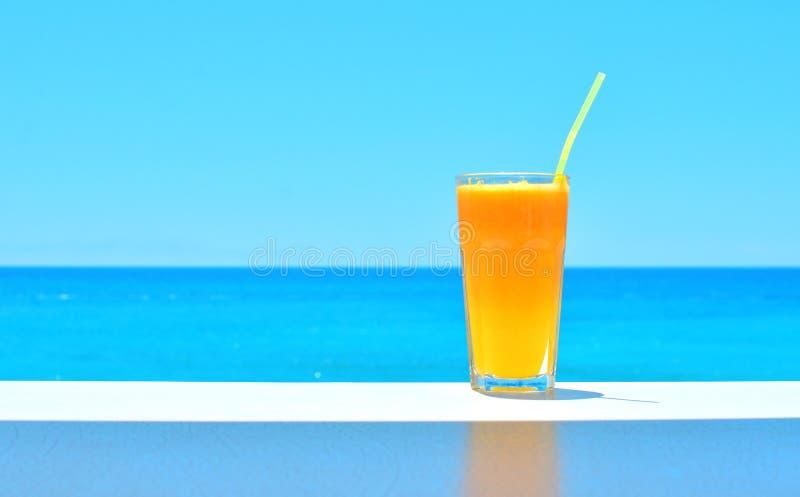 Jugo fresco anaranjado en un vidrio en la tabla con el contexto azul del mar imagenes de archivo