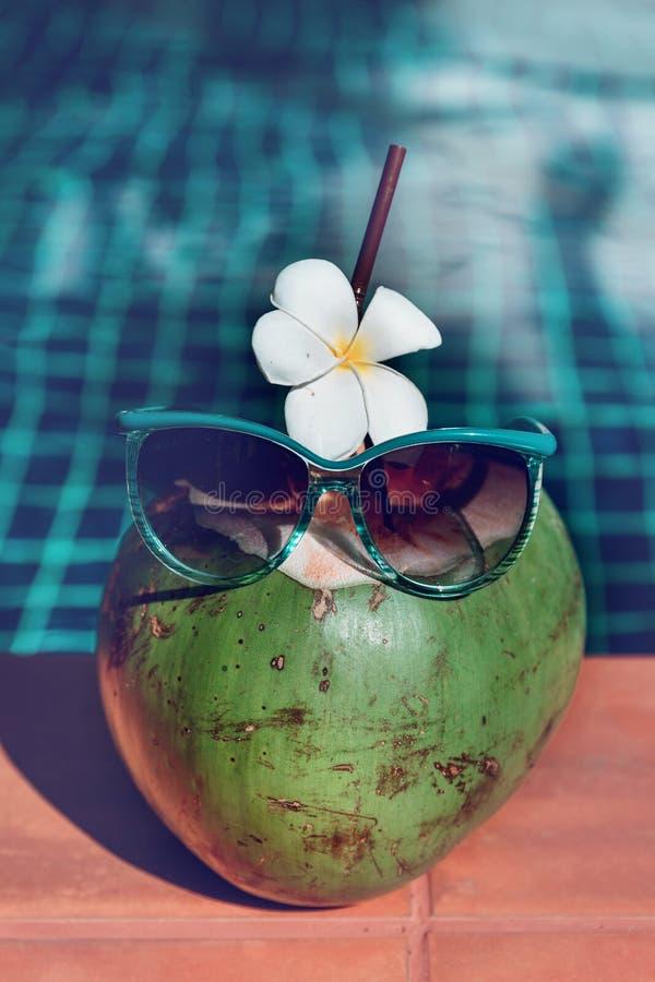 Jugo fresco del coco con la paja, la flor y las gafas de sol en la frontera foto de archivo