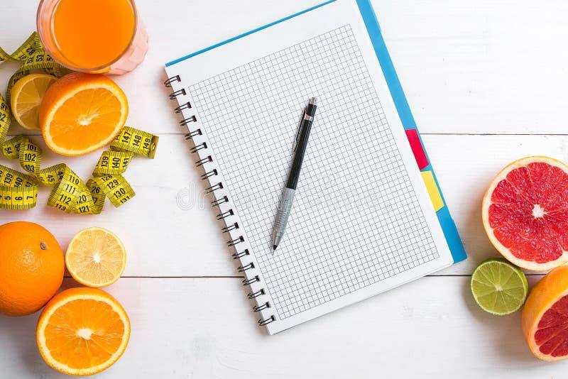 Jugo fresco en el vidrio de los agrios - limón, pomelo, naranja, cuaderno con el lápiz en el fondo de madera blanco foto de archivo