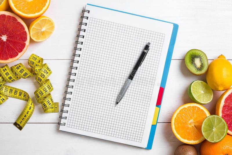 Jugo fresco en el vidrio de los agrios - limón, pomelo, naranja, cuaderno con el lápiz en el fondo de madera blanco fotos de archivo