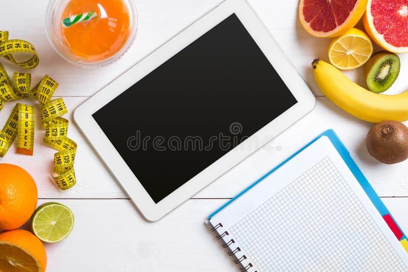 Jugo fresco en el vidrio de los agrios - limón, pomelo, naranja, cuaderno con el lápiz en el fondo de madera blanco imagen de archivo libre de regalías