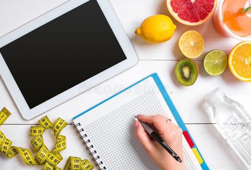 Jugo fresco en el vidrio de los agrios - limón, pomelo, naranja, cuaderno con el lápiz en el fondo de madera blanco imagen de archivo