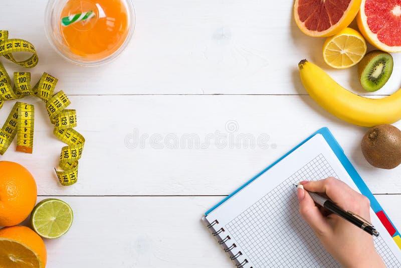 Jugo fresco en el vidrio de los agrios - limón, pomelo, naranja, cuaderno con el lápiz en el fondo de madera blanco imágenes de archivo libres de regalías