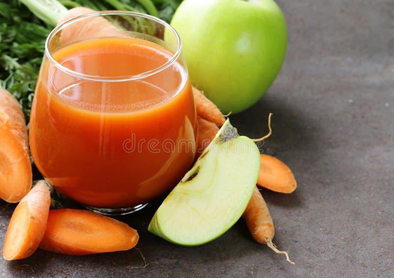 Jugo fresco orgánico natural de zanahorias y de la manzana verde fotos de archivo