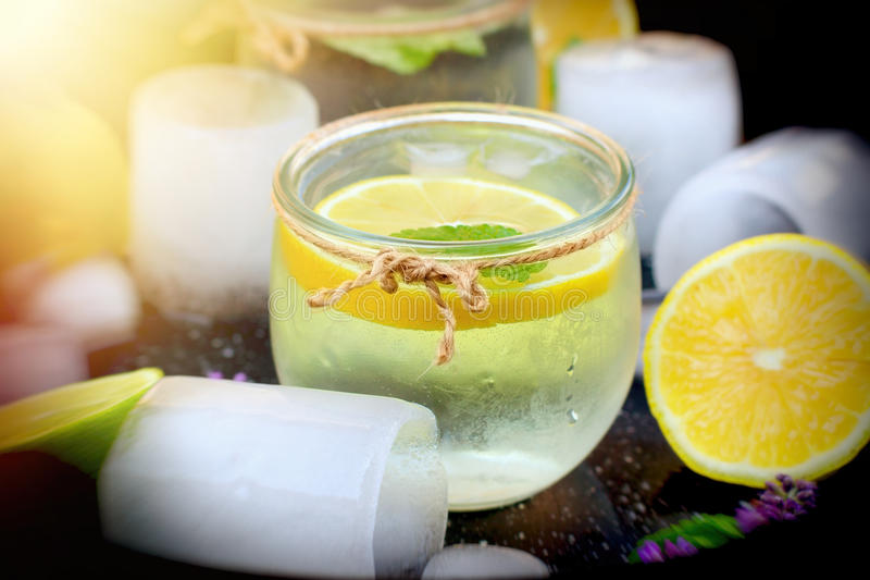 Jugo sano de la bebida con el limón y el hielo en vidrio - su disfrute del refresco adentro durante calor del verano fotos de archivo