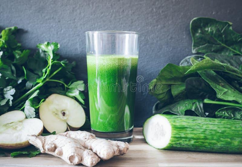 Jugo sano verde fresco del detox en el vidrio rodeado por las verduras y las frutas fotografía de archivo