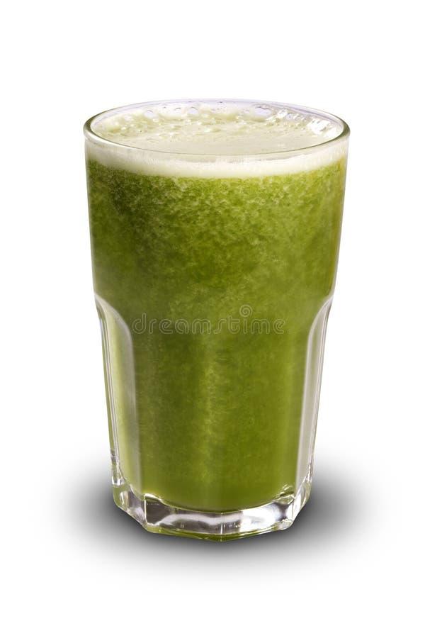 Jugo verde en un vidrio con la paja aislada en un backgroun blanco imagen de archivo